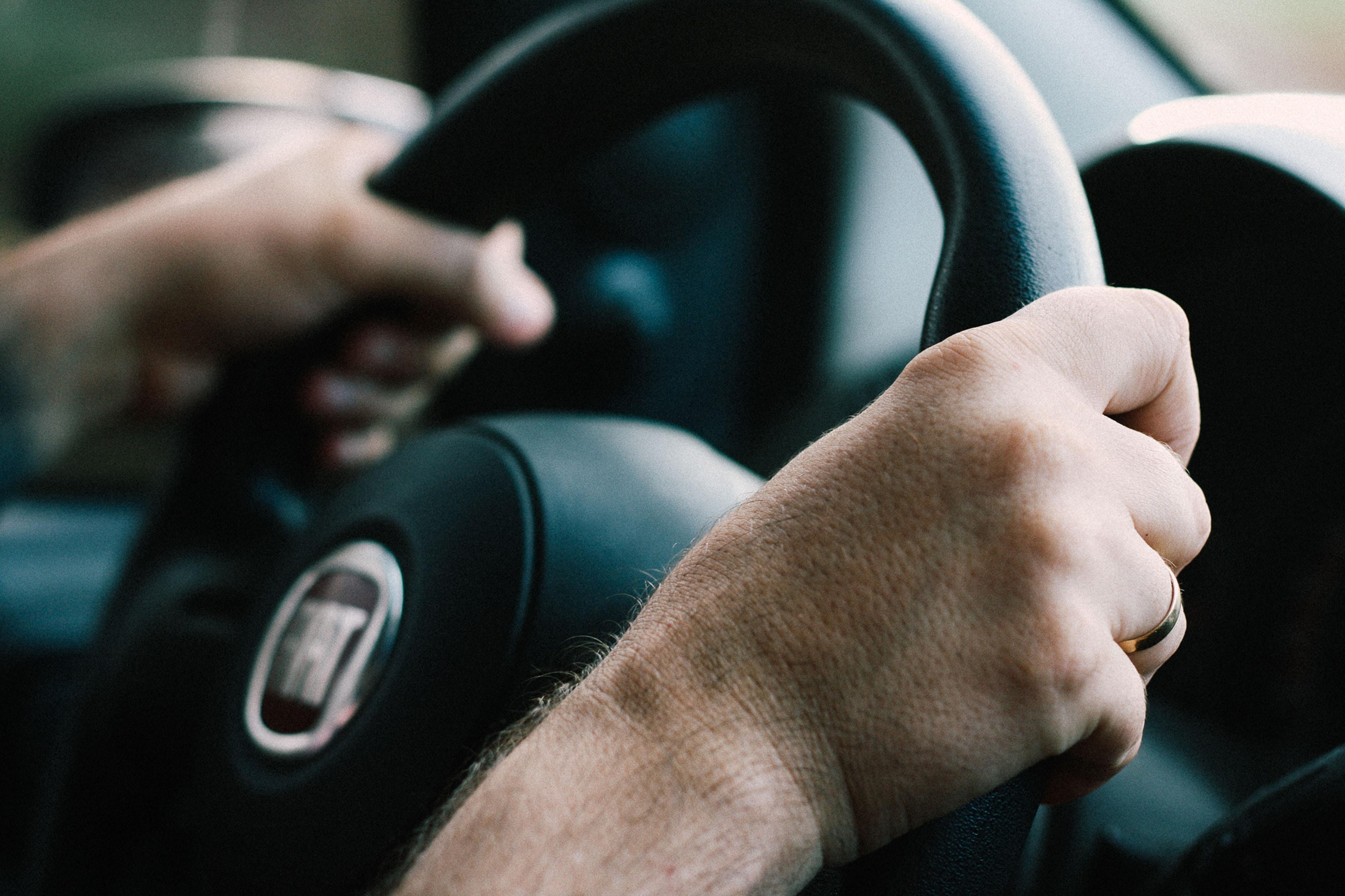 Gros plan sur les mains d'un homme au volant