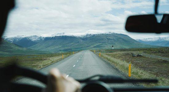 Vue sur une route et une montagne depuis l'habitacle d'une voiture